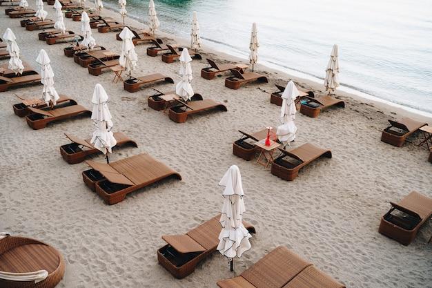 Espreguiçadeiras de plástico marrom com guarda-sóis em uma praia arenosa
