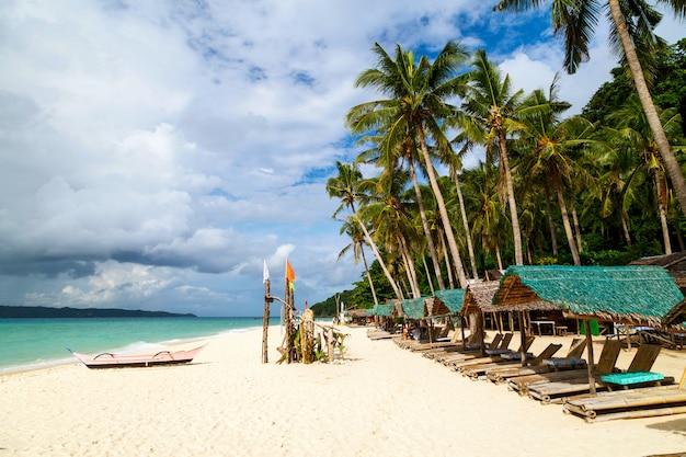 Espreguiçadeiras de praia sem pessoas na ensolarada praia tropical na ilha de boracay, filipinas