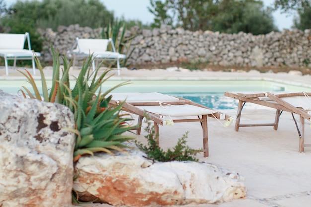Espreguiçadeiras dobráveis perto de uma piscina em um jardim ao pôr do sol