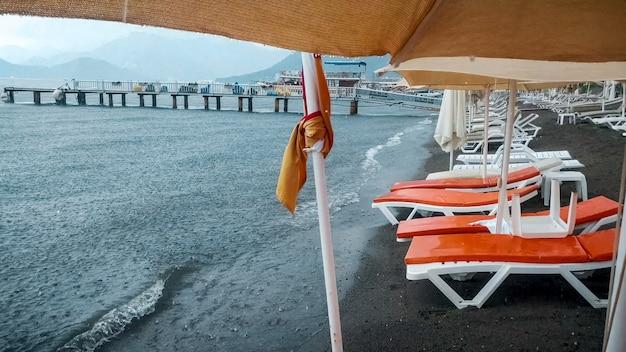 Espreguiçadeiras e guarda-sóis molhados na praia do mar durante uma forte tempestade de chuva.