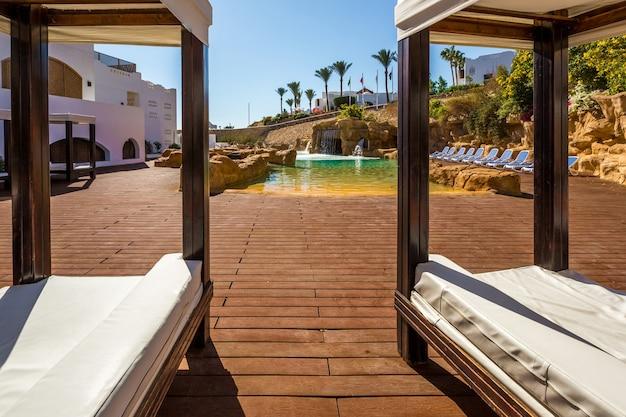 Espreguiçadeiras luxuosas e piscina com cascata artificial