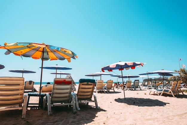 Espreguiçadeiras na praia tropical com céu calmo.