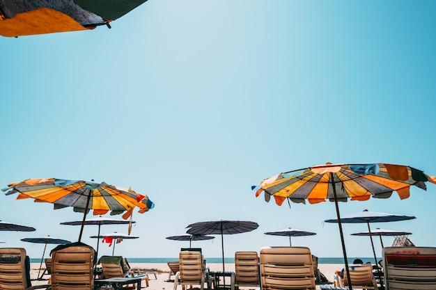 Espreguiçadeiras na praia tropical com céu calmo