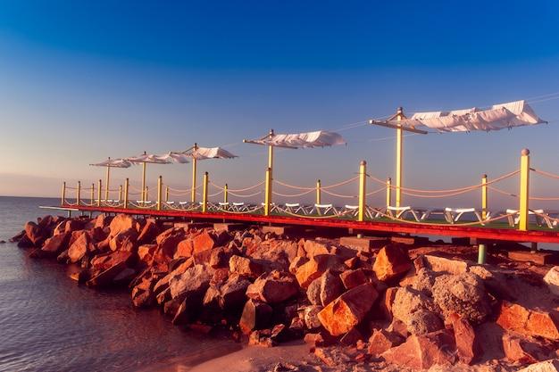 Espreguiçadeiras no píer rochoso junto ao mar