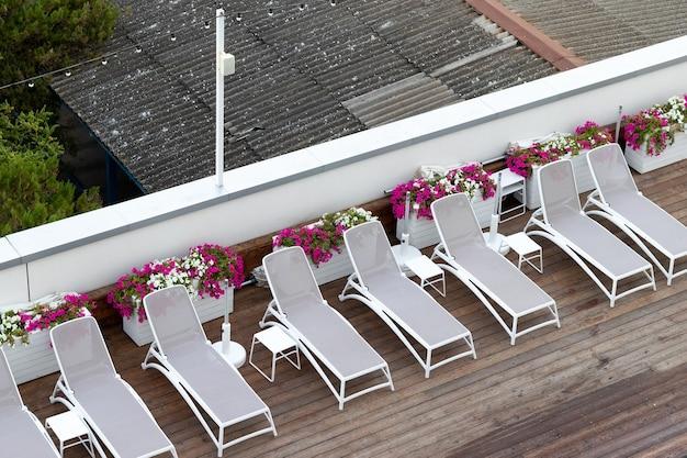 Espreguiçadeiras no piso de madeira junto à piscina do hotel. para relaxamento e recreação no hotel resort