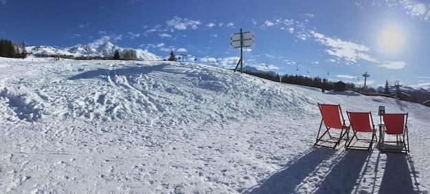 Espreguiçadeiras no terraço de inverno na neve nas pistas de esqui alpino