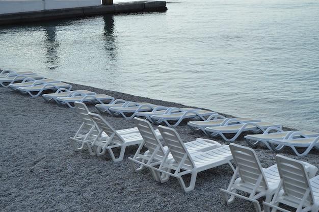 Espreguiçadeiras vazias à beira-mar no início da manhã, calmo, nascer do sol.
