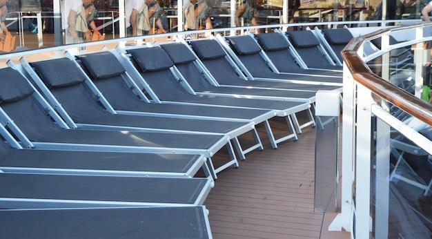 Espreguiçadeiras vazias espreguiçadeiras para relaxar no convés aberto de um navio de cruzeiro