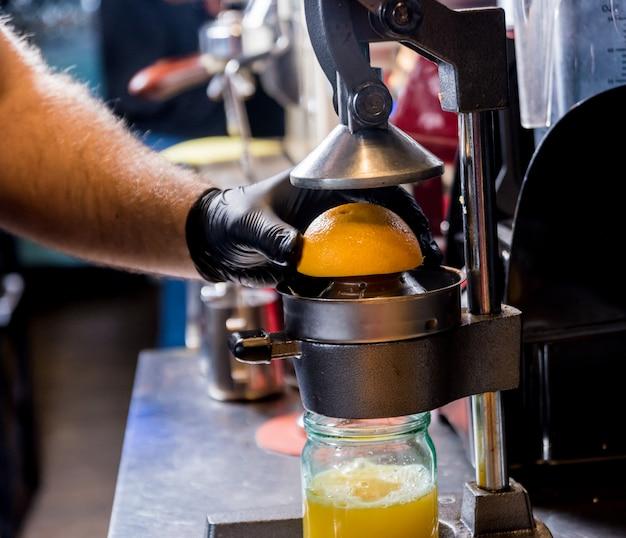 Espremedor manual de metal. preparação de suco de laranja espremido na hora