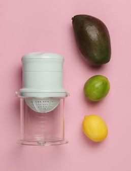 Espremedor manual de plástico e frutas tropicais em fundo rosa pastel. conceito de comida saudável. sucos espremidos na hora. vista do topo