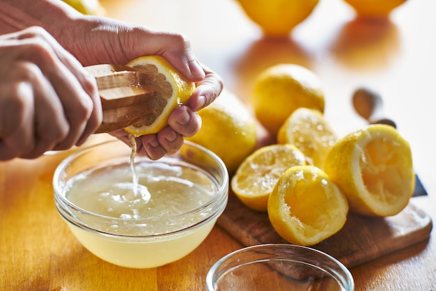 Espremendo suco de limão fresco com o alargador de madeira na tigela | Foto Premium