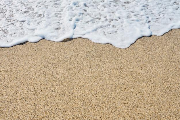 Espuma branca em uma praia arenosa