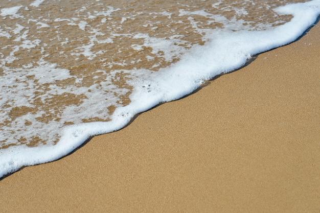 Espuma branca em uma praia arenosa Foto Premium