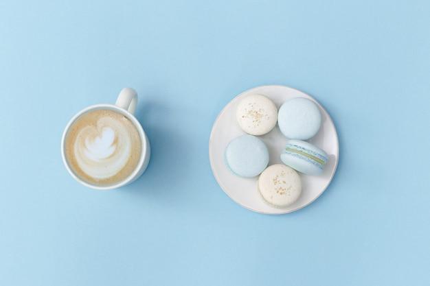 Espuma da arte do cappuccino de café na caneca grande e na placa branca com macarons saborosos no conceito doce azul brilhante do alimento. vista do topo. postura plana. composição de estilo minimalista.