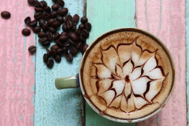 Espuma de café com leite estampado com grãos em uma mesa colorida retrô