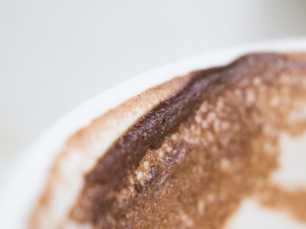 Espuma de café e mancha de café no copo branco close-up