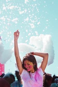 Espuma de festa sobre a garota dançando na celebração de holi