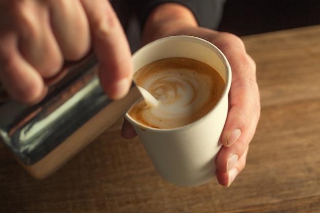 Espuma de leite derramada em um copo para viagem para formar um cappuccino.