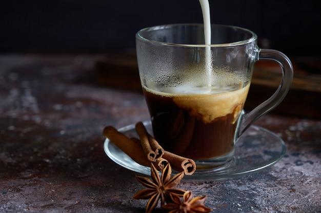 Espuma de leite está derramando no café preto quente cappuccino com açúcar, canela e anis