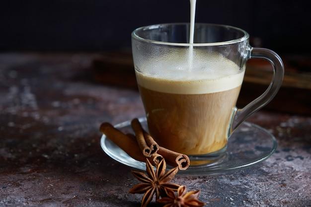 Espuma de leite está despejando café preto quente cappuccino com açúcar, canela e anis na superfície marrom escura