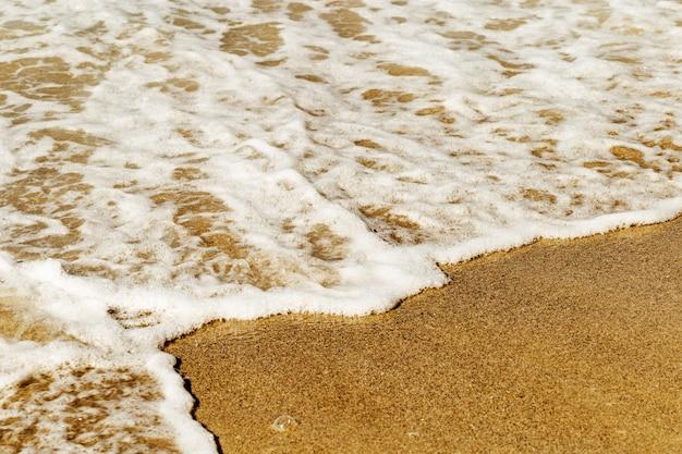 Espuma do mar na areia