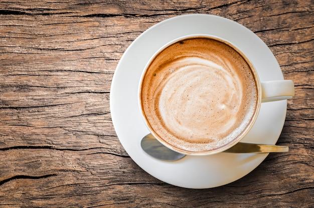 Espuma espumosa de café com leite quente cappuccino em copo branco na mesa de madeira velha