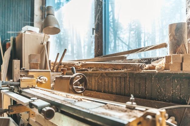 Espuma velha em pé de um carpinteiro velho por uma janela coberta de poeira e teias de aranha