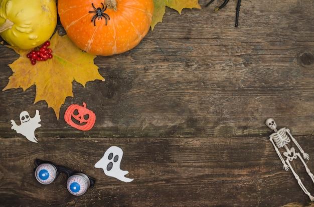 Esqueleto, abóboras e fantasmas em uma velha mesa de madeira