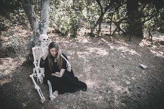 Esqueleto abraça senhora de leitura em roupas de bruxa