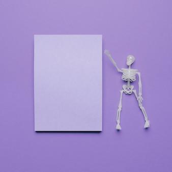 Esqueleto apontando para um espaço em branco para texto com vibrações de halloween