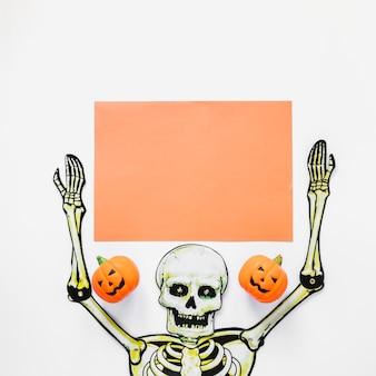 Esqueleto artesanal com pedaço de papel e abóboras