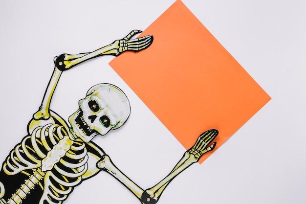 Esqueleto com folha de papel nas mãos
