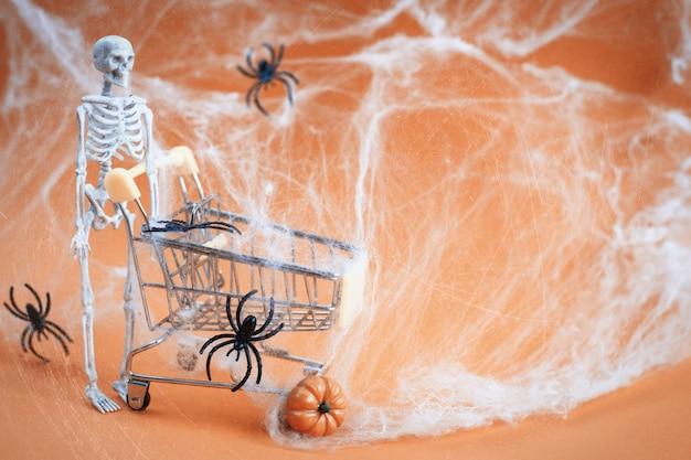 Esqueleto com uma abóbora perto das teias de aranha do carrinho e aranhas em um fundo laranja