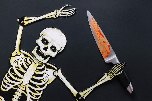 Esqueleto de papel com faca ensanguentada