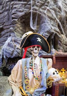 Esqueleto de pirata e baú de tesouro de pirata, jóias de ouro cheio com caveira de pirata.