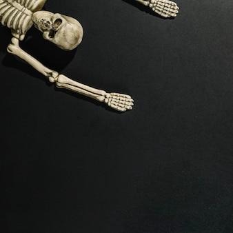 Esqueleto deitado com as mãos para cima