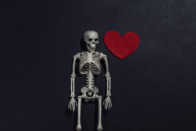 Esqueleto e coração decorativo vermelho sobre fundo preto. dia dos namorados ou tema de halloween.