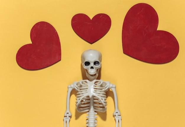 Esqueleto e corações decorativos vermelhos em um fundo amarelo brilhante. dia dos namorados ou tema de halloween.