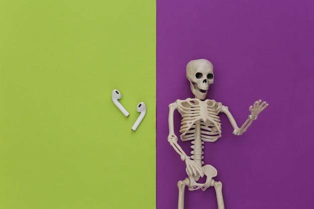 Esqueleto e fones de ouvido sem fio em fundo verde roxo.