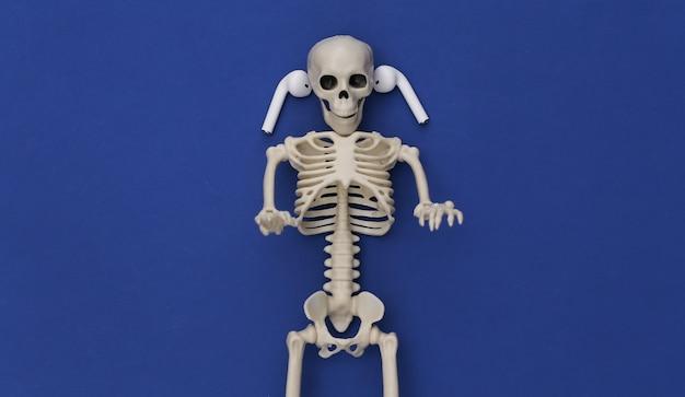 Esqueleto e fones de ouvido sem fio no fundo azul clássico.
