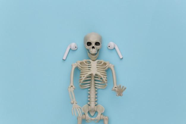 Esqueleto e fones de ouvido sem fio sobre fundo azul.