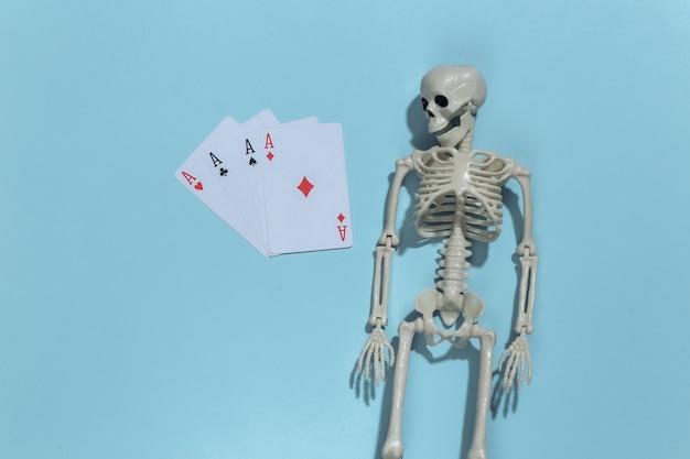 Esqueleto e quatro ases em fundo azul. vício em jogos de azar.