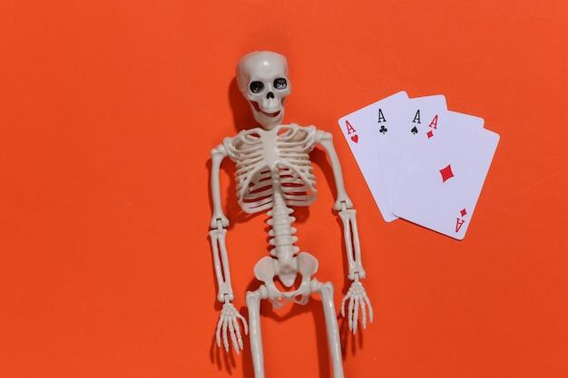 Esqueleto e quatro ases em um fundo laranja brilhante. vício em jogos de azar.
