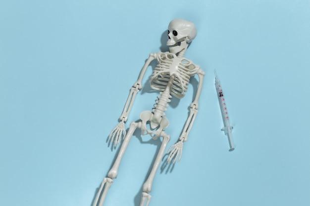 Esqueleto e seringa em um fundo azul brilhante. dependência de drogas.