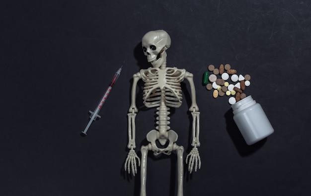 Esqueleto e seringa, frasco de comprimidos em um fundo preto. dependência de drogas.