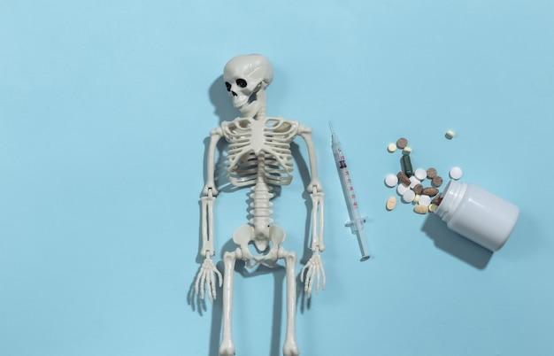 Esqueleto e seringa, frasco de comprimidos sobre um fundo azul brilhante. dependência de drogas.
