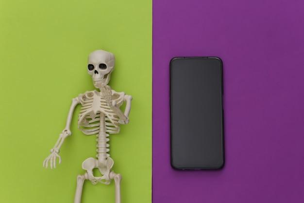 Esqueleto e smartphone em um fundo verde-púrpura. os efeitos nocivos das comunicações móveis