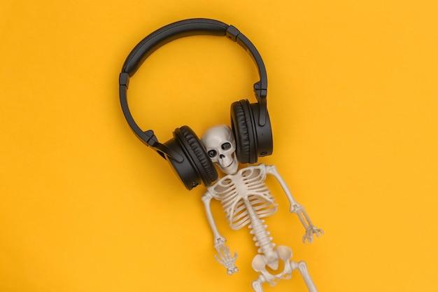 Esqueleto em grandes fones de ouvido estéreo pretos sobre fundo amarelo. vista do topo
