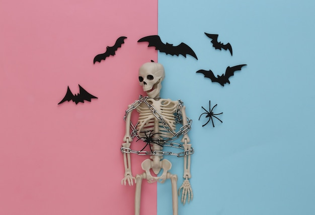 Esqueleto envolto em corrente de metal em pastel azul rosa com morcegos e aranhas. decoração de halloween, tema assustador