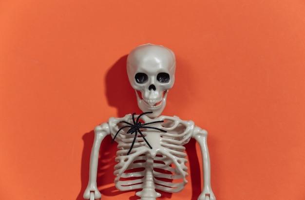 Esqueleto esculpido com aranha em fundo laranja brilhante. tema de halloween.